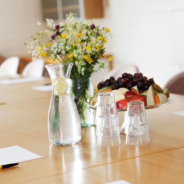 bord med frukt, blomsterbukett og glass med vann