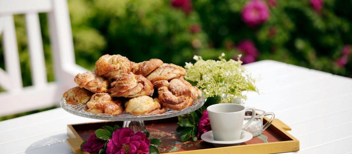 Bakevarer, blomster, kaffe plasser på serveringsbrett
